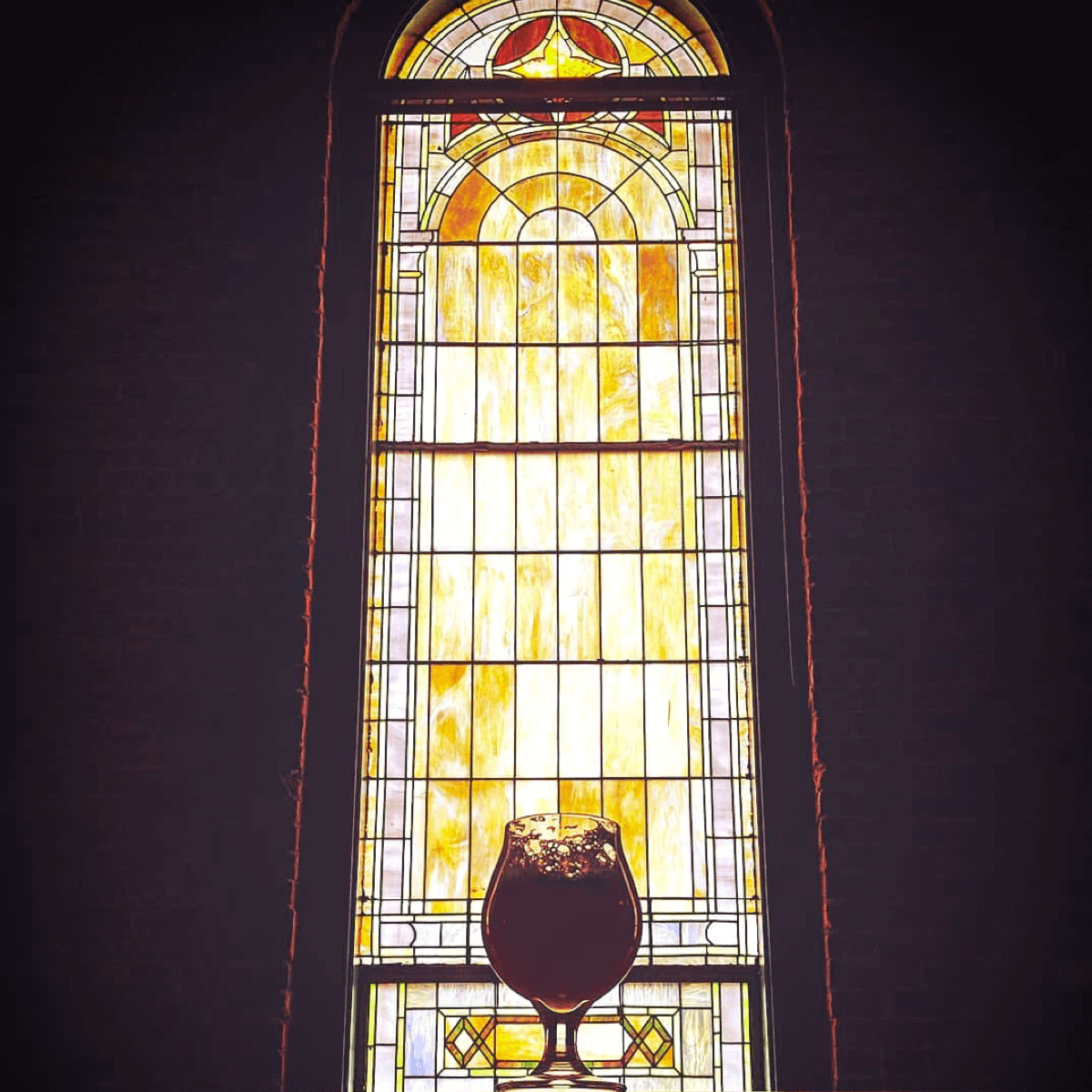 Un verre de bière face aux vitraux, une image qui fait penser à la prière de la bière - Crédit Photo : @sam_i_gram
