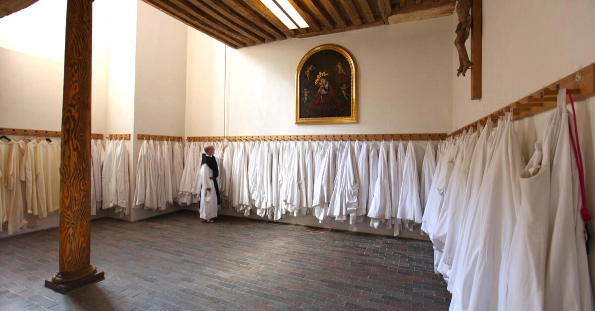 Un moine de l'abbaye de Sept-Fons qui choisit parmi les nombreuses aubes, liées aux nombreux moines de l'abbaye - © Abbaye de Sept-Fons