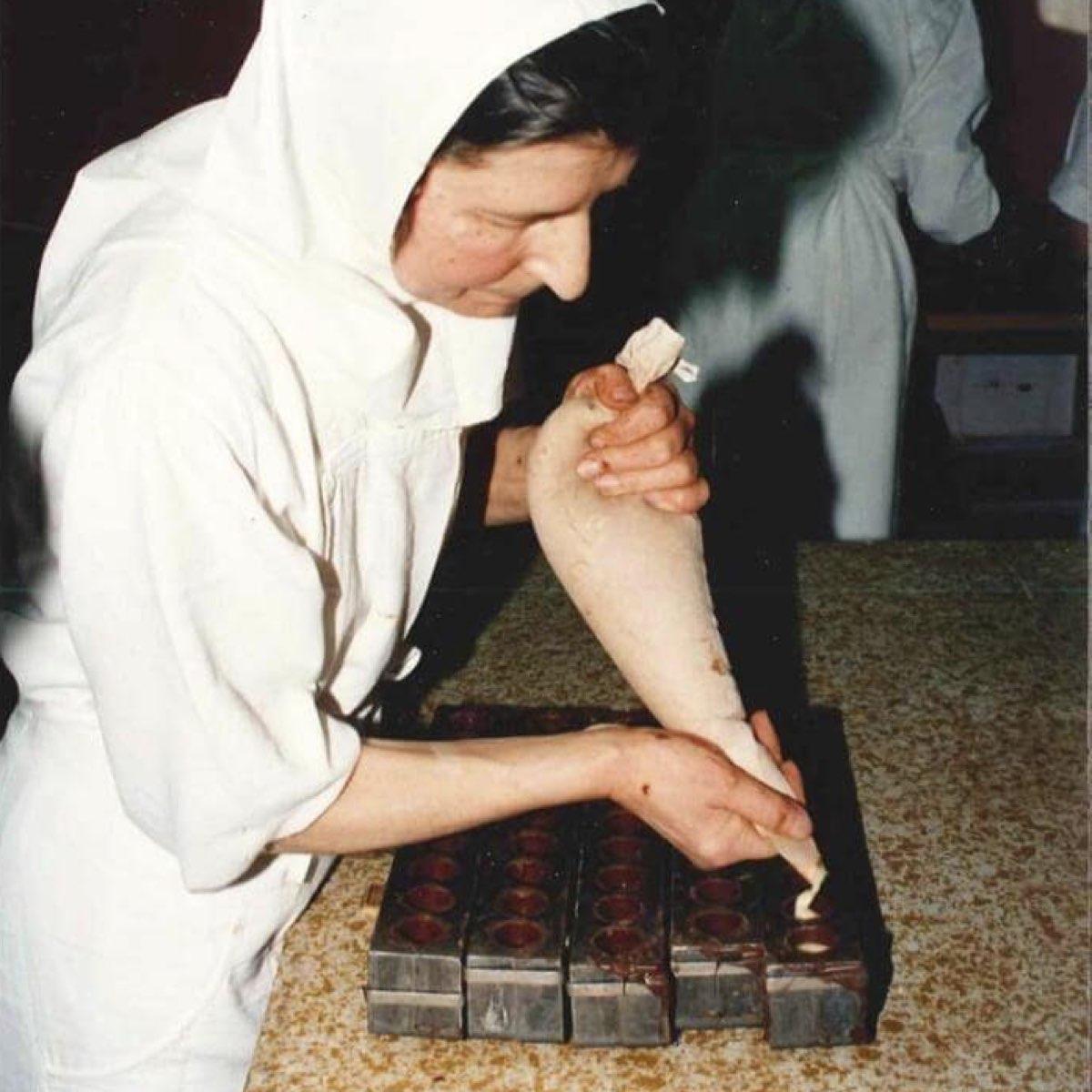 Quelle artiste cette sœur chocolatière ! Elle tient à la main ce qu'on appelle une poche à douille en pâtisserie. ©Abbaye Igny